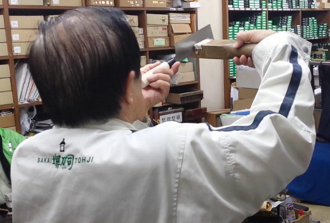 artigiano giapponese che controlla la linea della lama del coltello con un calibro di legno verificando che sia perfettamente dritta