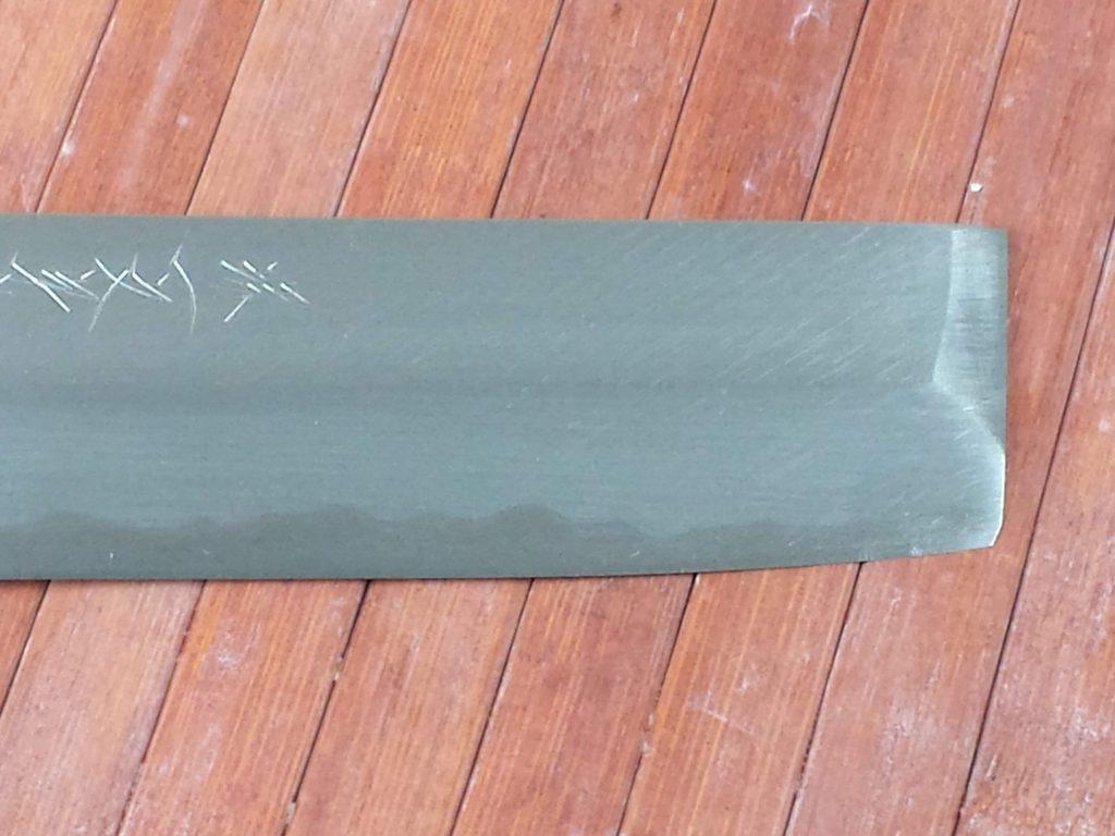 lama di un coltello da cucina giapponese Usuba stile Kanto dove risulta attenuata la linea tra ferro dolce e acciaio duro a causa del potere abrasivo della polvere di allumina bianca