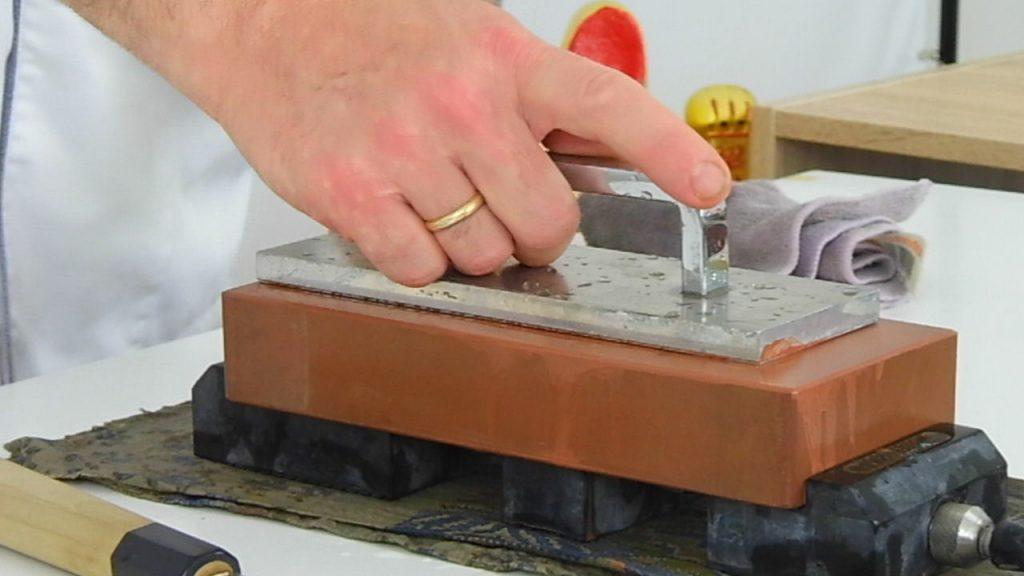 operazione di rettifica della pietra da affilatura di grana 1000 per rendere ottimale la planarità della superficie prima di procedere con l'affilatura
