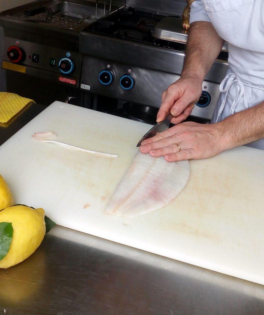 eliminazione delle spine della linea centrale da un filetto di pesce rombo con un coltello Deba in stile tradizionale giapponese