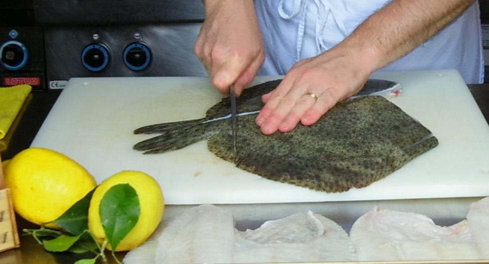 taglio della coda di un pesce rombo con un coltello Deba in stile tradizionale giapponese
