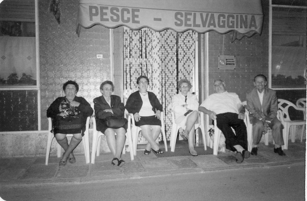 Persone gioiose sedute all'esterno di un'attività commerciale promiscua (pesce e selvaggina) in una foto scattata nel paese di Codigoro intorno agli anni 80